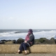 A woman is protecting her face against the tough winds on the Pier of Hoek van Holland