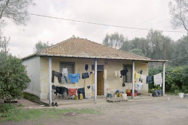 """Drosi (Gioia Tauro), 2016. Temporary shelter set in a citrus grove in the plain of Gioia Tauro. According to CGIL (union organization) in Italy there are about 400 thousand foreign daily laboures who find work through the """"caporalato"""" (system of directly hiring farm labour for very low wages by landowner's agents).Drosi (Gioia Tauro), 2016. Rifugio temporaneo in un agrumeto della piana di Gioia Tauro. Secondo la CGIL in Italia sono circa 400 mila i lavoratori stagionali stranieri che trovano lavoro attraverso il caporalato."""